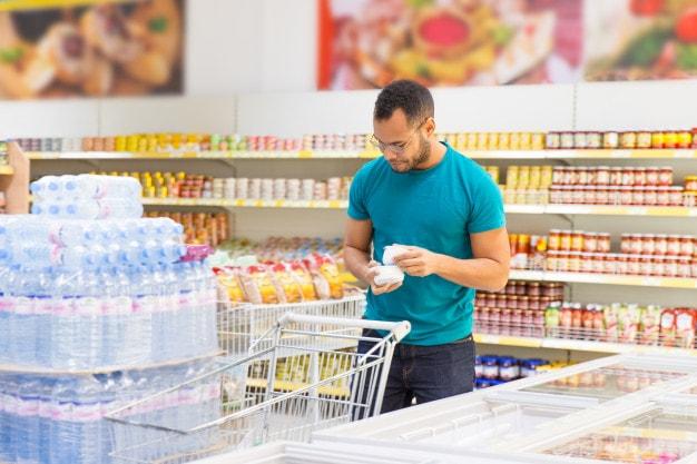 ผู้ชายหยิบสินค้าจากตู้แช่ในร้านมินิมาร์ท