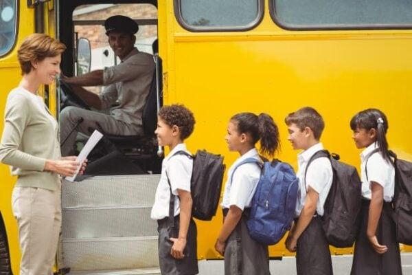 cute schoolchildren waiting get school bus
