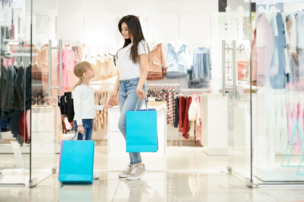 two pretty clients holding shopping bags posing store